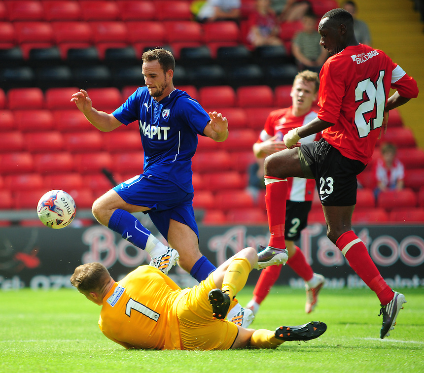 Lincoln City's Paul Farman saves at the feet of Chesterfield's Dan Gardner<br /> <br /> Photographer Chris Vaughan/CameraSport<br /> <br /> Football - Friendly - Lincoln City v Chesterfield - Saturday 19th July 2014 - Sincil Bank Stadium - Lincoln<br /> <br /> &copy; CameraSport - 43 Linden Ave. Countesthorpe. Leicester. England. LE8 5PG - Tel: +44 (0) 116 277 4147 - admin@camerasport.com - www.camerasport.com