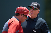 Third base umpire Jim Schaly chats with North Carolina State Wolfpack third base coach Chris Hart during the game against the Northeastern Huskies at Doak Field at Dail Park on June 2, 2018 in Raleigh, North Carolina. The Wolfpack defeated the Huskies 9-2. (Brian Westerholt/Four Seam Images)