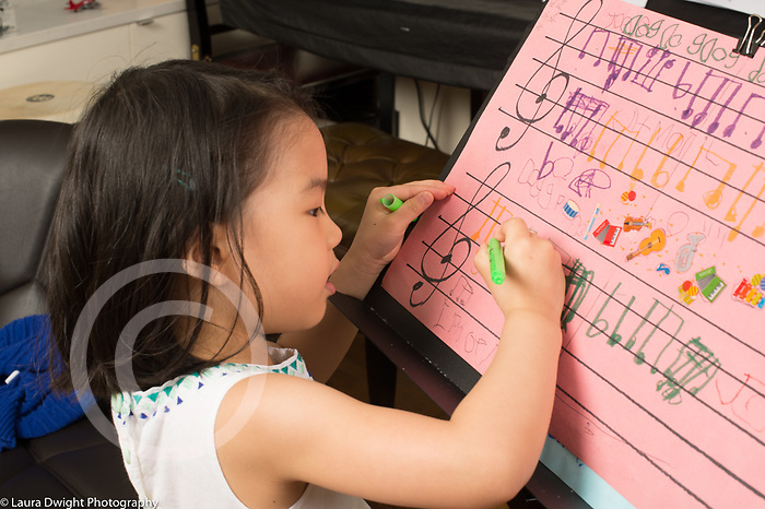 4 year old girl writing musical notes on paper on music stand