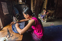 Myanmar/Burma, Mandalay. Khin Than Su, tailoring. Khin Than Su is 27 years old and runs a home based tailoring business. She works a Burmese foot pedal sewing machine and sews textiles and lungi clothing that her sister in Yangon can help her sell. With the help of her niece, the two of them can make about 400 a day and they go door to door selling them for $6 each. She also fills factory orders but then gets only $1 a lungi. She makes about $8 a day. She is still waiting for BRAC to approve a $300 loan to buy more lungi material. She also sells hair clips, slippers and small goods to help supplement her income. Someday she would like to buy an electric sewing machine. She is single, has six siblings and is currently living with her parents. Model released, MR-Myanmar-145
