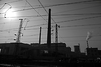 Daytime landscape view from a train of a commercial factory building site with cooling towers and smokestacks near Dàtóng Shì Chéng Qū in Shānxī Province, China  © LAN