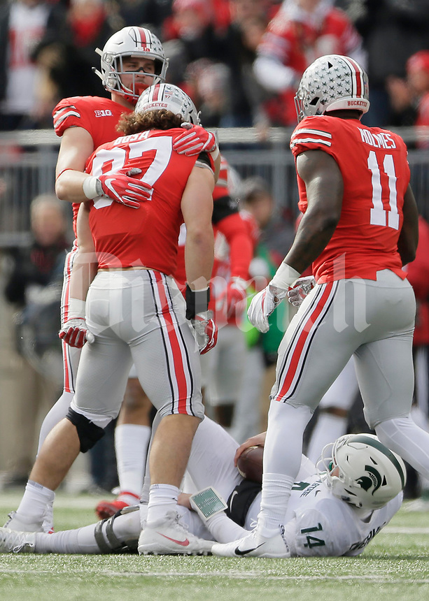 Ohio State Buckeyes defensive end Sam Hubbard (6) hugs defensive lineman Nick Bosa (97) as defensive end Jalyn Holmes (11) runs in to celebrate a sack of Michigan State Spartans quarterback Brian Lewerke (14) during the first quarter of the NCAA football game at Ohio Stadium in Columbus on Nov. 11, 2017. [Adam Cairns/Dispatch]