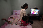 A woman and her daughter watch a video of a wedding held by their relatives, as they sit in their room in a building inhabited by Eritrean asylum-seekers in Jerusalem.