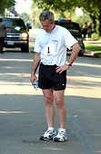 Washington, DC - June 22, 2002 -- United States President George W. Bush bows his head after completing a 5K run as part of the President's Fitness Challenge at Fort McNair in Washington on 22 June, 2002.<br /> Credit: Ron Sachs / Pool via CNP