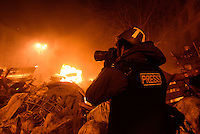 A press-photographer wearing a helmet to protect himself while reporting from the barricades during protests. Kiev, Ukraine. Feb. 18, 2014. (Photo by Msyslav Chernov / UnFrame)