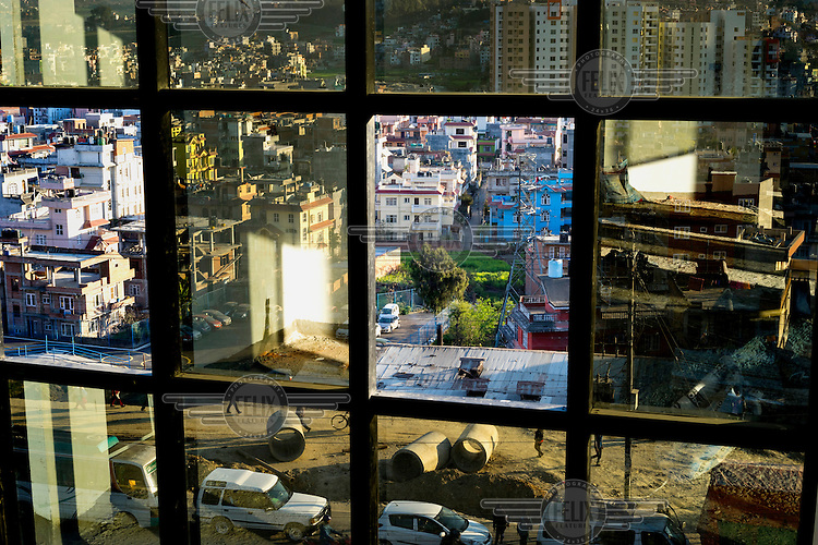 Construction materials and pedestrians are seen out of the window of a new building in Kathmandu. Only a few years ago, this was the edge of the city, and green rice paddies filled the space now occupied by high-rise apartment blocks and concrete homes. Yet hidden amid the maze of new buildings are tiny, ancient shrines around which the development bends itself. <br /> Over the past few years, Kathmandu has undergone a period of rapid urbanization, however throughout this process it has remained curiously unique in its loyalty to its cultural history. The result is a city in which astrologers are consulted about future developments by retail investors, and concrete high-rise buildings haphazardly wind their way around tiny ancient shrines.