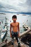 PHILIPPINES, Palawan, Puerto Princesa, young fisherman stands in front of fishing boats at Liberty Fishing Village