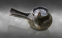 Phrygian grey ceramic vessel with a strainer and long spout from Gordion. Phrygian Collection, 8th-7th century BC - Museum of Anatolian Civilisations Ankara. Turkey. Against a grey background
