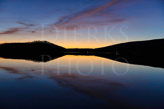 Sunset sky mirrored across calm lake water, reflecting in pink, blue, and yellow colors, beauty in nature Canoe Creek State Park in Pennsylvania, PA, USA.