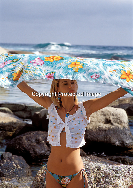 diinmed00046 Industry Media. A swimsuit fashion shoot for Elle Magazine at Bantry Bay beach in Cape Town , South Africa on August 21, 2002. A white model is holding a towel over her head..©Per-Anders Pettersson/ iAfrika Photos