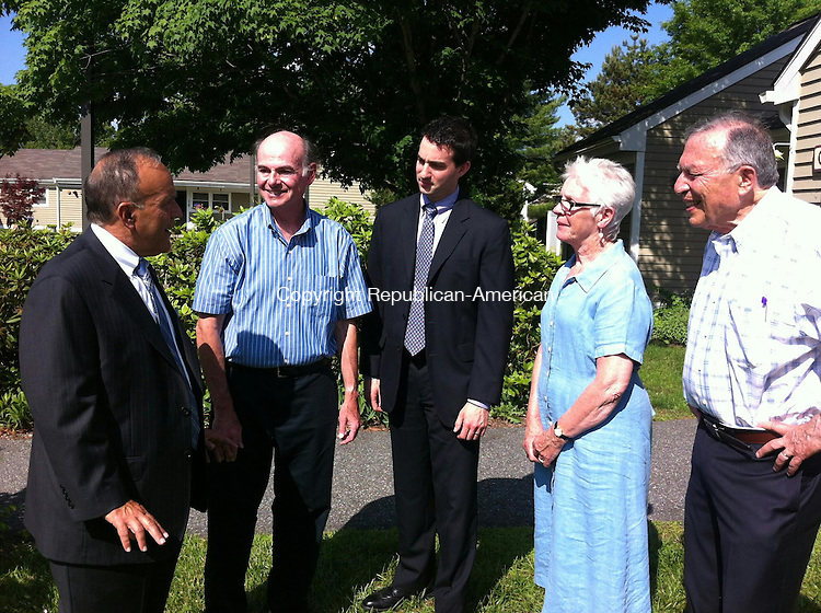 SOUTHBURY, CT. - 10 June 2015 - 061015CG01 - John F. Trentacosta, left, president of Newtown Savings Bank, discusses the Pierce Hollow Village project in Southbury with, from left, Pierce Hollow board member Gerry Klein; Matthew F. Mihalcik, manager of the bank's Southbury branch; and Pierce Hollow board members June Bennett and Joel Abramson. The bank gave a donation to the board Wednesday. Chris Gardner Republican-American