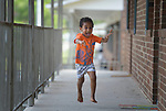 Three-year old Youel, a resettled refugee from Eritrea, runs along the balcony of the apartment complex where he lives with his mother in Durham, North Carolina. The family was resettled in Durham by Church World Service, which resettles refugees in North Carolina and throughout the United States.<br /> <br /> Photo by Paul Jeffrey for Church World Service.