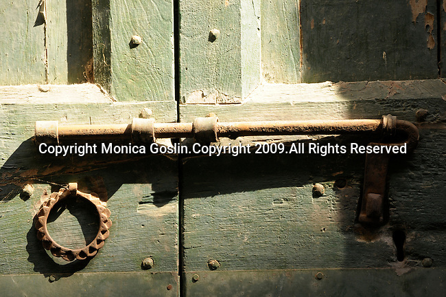 A rusted old lock on a green wooden door in Rezzonico, a town on Lake Como, Italy.