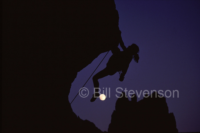 A photo of a woman rock climbing by the full moon at Smith Rock State Park in Oregon