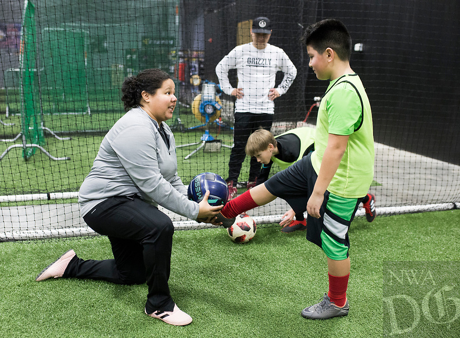 NWA Democrat-Gazette/CHARLIE KAIJO Coach Sarita Saavedra helps Kian Moreno, 9, of Rogers (from left) with juggling skills during a three-day New Year's Soccer Camp, January 4, 2019 at Strike Zone Training Academy in Rogers. <br />