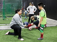 """NWA Democrat-Gazette/CHARLIE KAIJO Coach Sarita Saavedra helps Kian Moreno, 9, of Rogers (from left) with juggling skills during a three-day New Year's Soccer Camp, January 4, 2019 at Strike Zone Training Academy in Rogers. <br /><br />The Specialized Soccer Academy hosted a three-day soccer camp to help build confidence in young athletes.<br /><br />""""If they build confidence in a sport they feel like they have something that's theirs,"""" said Coach Sarita Saavedra. """"They help themselves get better and that translates to confidence in the classroom or anything.""""<br /><br />The kids worked on juggling skills, one-versus-one practice and scrimmages."""