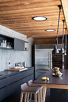 The chalet's contemporary kitchen features a stainless steel American fridge and a series of pendant lights above a free-standing breakfast table