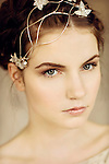 Close portrait of young woman with silver headpiece and braided hair looking into the camera
