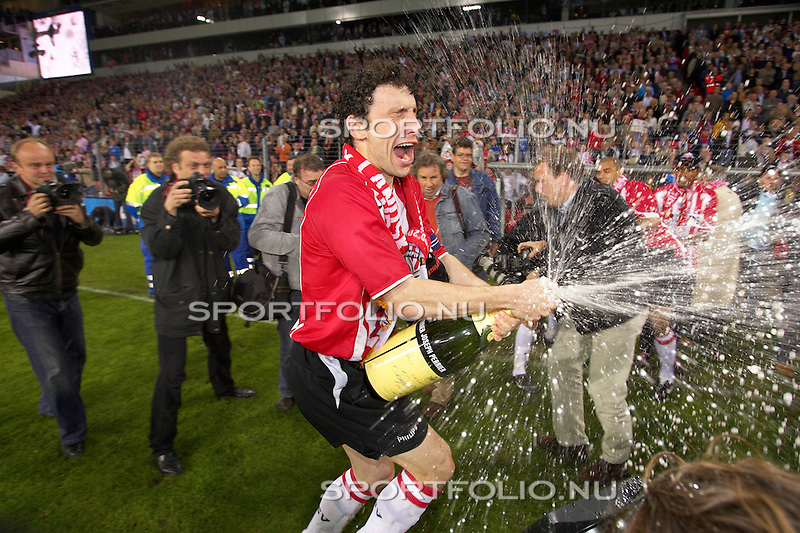 Nederland, Eindhoven, 23 april 2005.Eredivisie .Seizoen 2004-2005.PSV is kampioen van Nederland .Aanvoerder van PSV, Mark van Bommel spuit met een Magnum fles champagne zijn ploeggenoten onder.