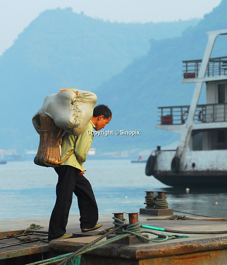 Porters carry goods onto cargo boats using traditional bamboo baskets below the three Gorges Dam in Yichang, China. The goods will be taken up-stream to the new cities and towns that have been built as part of the Three Gorges Dam Project. .18 May 2006.