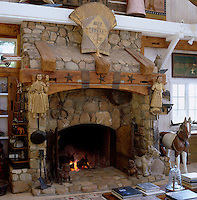 The open-plan living room is dominated by a vast stone fireplace and decorated with American Folk Art