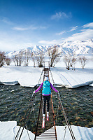 A skier crosses a bridge over a river with her skis on while ski touring in the Suusamyr region of Kyrgyzstan
