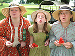 Photo by Phil Grout..Some of the staff of the Carroll County Farm Museum join in the.old fashioned Fourth of July fun spitting watermelon seeds..Dressed in their 19th Century garb are Ann Campbell (left),.Amber Binley and Pat Brodowski.  Visitors to the Farm Museum.dodged the rain and enjoyed the special activities.