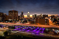Sunset falls on the downtown Austin Skyline as the I-35 Makeover Project Parking garage performs its colored light show in purple