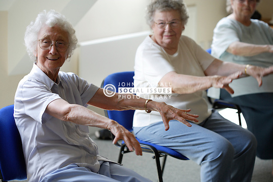 Group of older women doing arm exercises at a keep fit class,