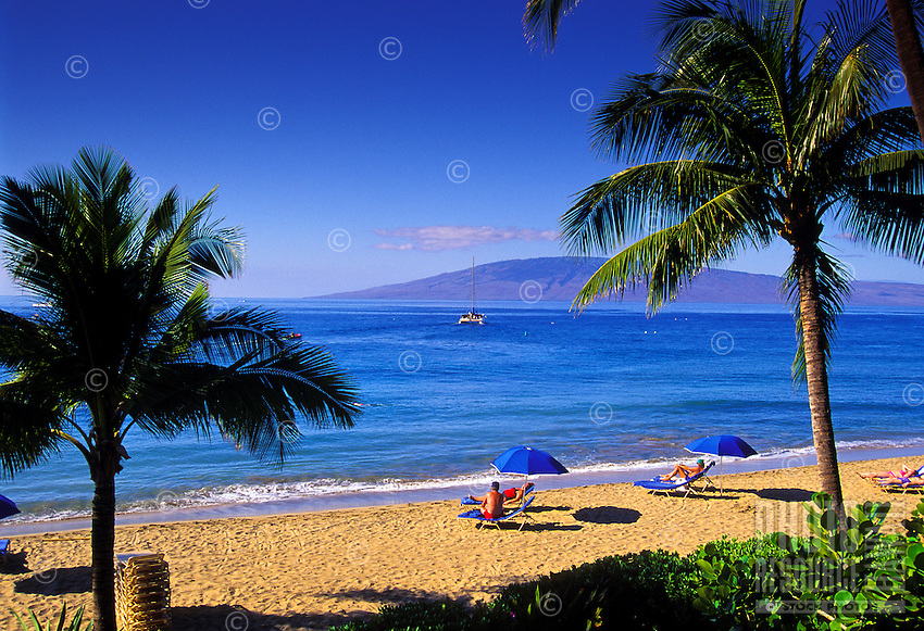 People relax on Kaanapali Beach with palm trees and a view of Lanai.