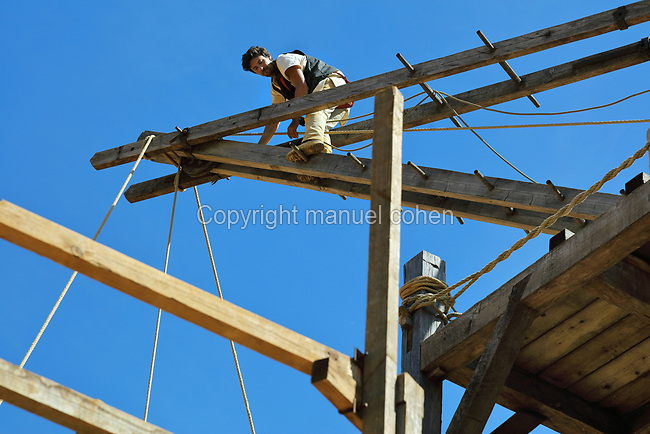Worker carrying out maintenance on the lifting gear or squirrel cage with double drum, on the building site in the courtyard at the Chateau de Guedelon, a castle built since 1997 using only medieval materials and processes, photographed in 2017, in Treigny, Yonne, Burgundy, France. The Guedelon project was begun in 1997 by Michel Guyot, owner of the nearby Chateau de Saint-Fargeau, with architect Jacques Moulin. It is an educational and scientific project with the aim of understanding medieval building techniques and the chateau should be completed in the 2020s. Picture by Manuel Cohen