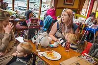 A mother sitting at a table talks to a friend while breastfeeding her two year old daughter in the family restaurant and play area of a pub.<br /> <br /> Lancashire, England, UK<br /> <br /> Date Taken:<br /> 07-01-2015<br /> <br /> &copy; Paul Carter / wdiip.co.uk