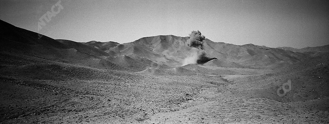 Weapons and deadly explosives found by Handicap International are blown up in the desert outside of town. Herat, Afghanistan. July, 2003.