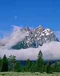 A full moon and low clouds surround the Cathedral Group peaks, Grand Teton National Park, Wyoming