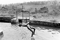 Burundi. Karuzi Province. Buhiga. Young boy naked jumps and takes a bath in a water chanel used to irrigate the fields. Lock gate. © 2000 Didier Ruef