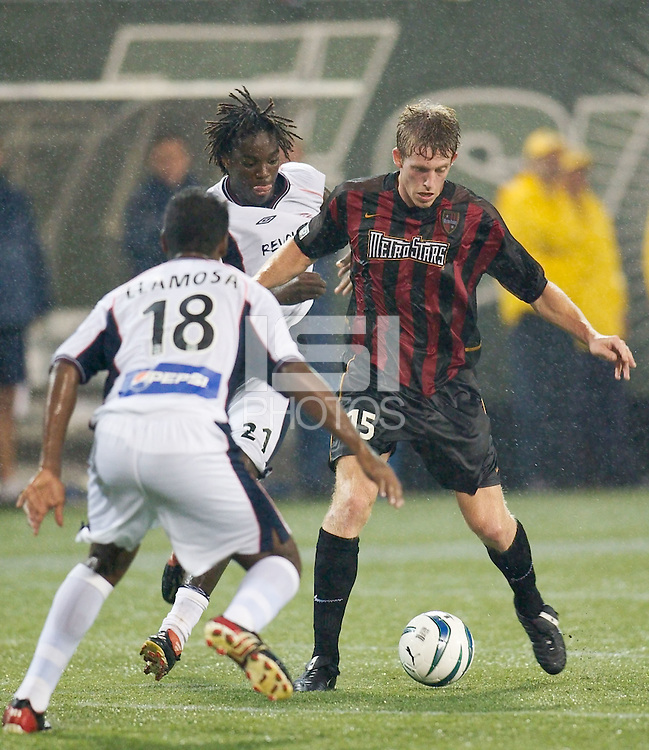 John Wolyniec of the MetroStars is marked by Carlos Llamosa and Shalrie Joseph of the Revolution during heavy rains in the first half. The NY/NJ MetroStars were defeated by the New England Revolution 2-1 on 9/13/03 at Giant's Stadium, NJ..