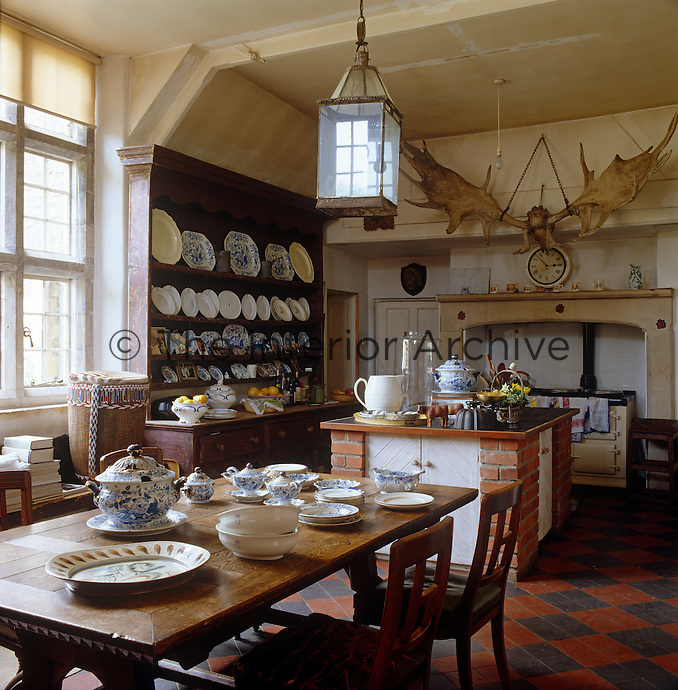 A large set of antlers hangs above the range in this country kitchen and the dresser displays a collection of plates