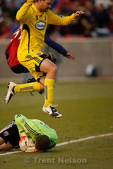 Columbus Crew defender Chad Marshall (14) and Real Salt Lake midfielder Andy Williams (77) leap over Columbus Crew goalkeeper William Hesmer (1). Real Salt Lake vs. Columbus Crew, MLS Soccer playoffs Saturday, October 31 2009 at Rio Tinto Stadium in Sandy.