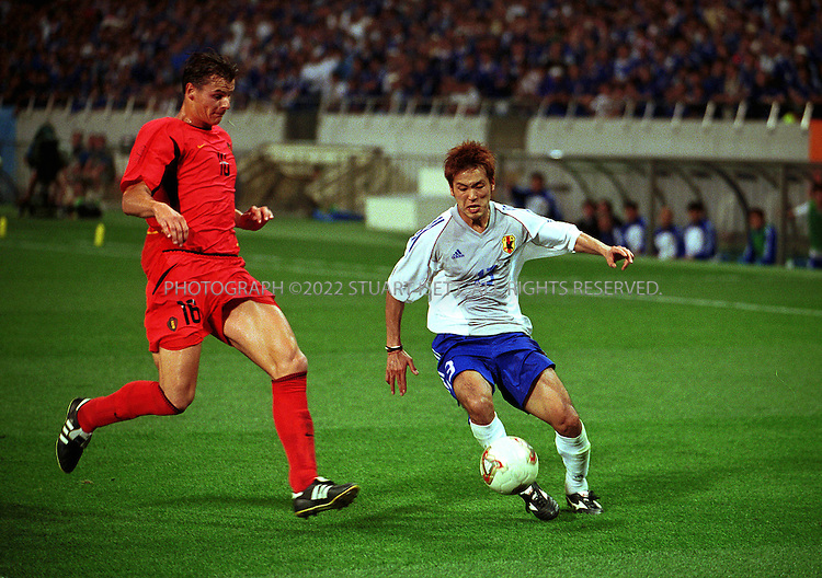 6/4/2002--Saitama, Japan..Japanese player Atsushi Yanagisawa tries to cross the ball  while Belgian Jacky Peeters tries to block him during a 2002 World Cup Group H match Japan vs Belgium in Saitama, Japan. The match ended 2-2. The other teams playing in Group H are Russia and Tunisia. ..All photographs ©2003 Stuart Isett.All rights reserved.This image may not be reproduced without expressed written permission from Stuart Isett.