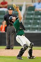 Greensboro Grasshoppers catcher Tony Caldwell #14 settles under a foul pop fly during the South Atlantic League game against the Kannapolis Intimidators at CMC-Northeast Stadium on June 12, 2012 in Kannapolis, North Carolina.  The Intimidators defeated the Grasshoppers 2-1.  (Brian Westerholt/Four Seam Images)
