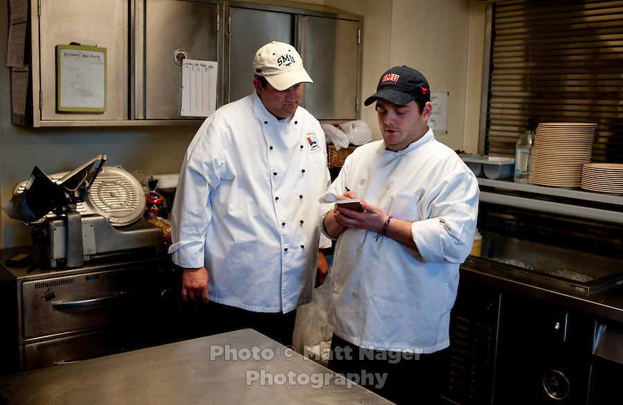 Professional Chef Ken Cobb (cq, left) discusses the evenings menu with private chef Brent Moore (cq, right) at the Sigma Alpha Epsilon fraternity house on the Southern Methodist University campus in Dallas, Texas, Friday, january 20, 2011. Some high-end chefs have found professional salvation from an unlikely location: Fraternity Row. Cobb employs a pair of interns from the Dallas Culinary Institute, where he once served as lead instructor, to help him cook three meals every weekday for another pair of frat houses on SMU's campus...Matt Nager for The Wall Street Journal