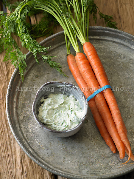Bunch of carrots with tops and fresh herb sour cream dip