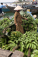 A female coolie helps to shift bananas destined for the market in Hoi An, Vietnam, from the boat on which they have arrived.