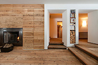 The wood clad interior gives a dramatic sense of space to the living room
