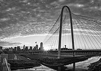Dallas BW Margaret Hunt Hill Bridge Pano -  We capture this sunrise as the sun rays just pop up over the rail in the early morning at the Margaret Hunt Hill Bridge in downtown Dallas in black and white.  You can see the Dallas skyline in the background. The sky filled with these clouds with wonderful pink and orange colors in the morning light over the Margaret Hunt Hill Bridge.  The Margaret Hunt Hill bridge has become a popular spot for locals and tourist alike, it is a beautiful bridge that is 400 ft high, which was designed by Santiago Calatrava the first part of the Trinity project. The bridge was complete in 2012 and has become a major landmark and iconic structure that has become a part of the cities skyline images that draw tourist and locals alike. Dallas skyline has some of the tallest skyscrapers like the Bank of America, Fountain Plaza, Chase Tower, and the popular Reunion Tower. The population for Dallas is almost 2 million but the Dallas Fort Worth area or DFW has a population over 7 million.  Dallas got it root from the railroad when it was a major inland transportation hub for cotton, cattle and later on oil.  It is now a modern city with some of the tallest buildings in Texas second only to Houston.  It is the third most populous city in Texas after Houston and San Antonio.  There are many fortune 500 companies in Dallas such as AT&T, Southwest Airlines, Sprint, 7 Eleven, and many other tech companies, which has seal Dallas as leader in the business world. It also has a vibrant art district.