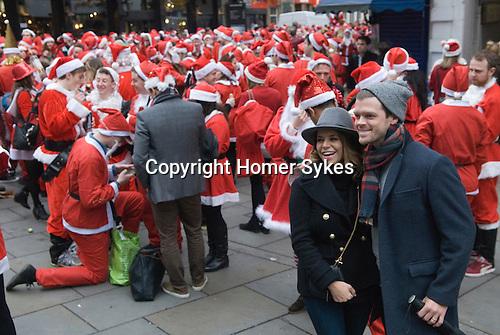 Tourist Lndon Christmas having their photograph taken with a group of Father Christmas's