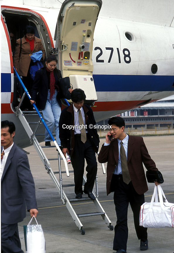 Businessmen getting off a plane use their  mobile phones at Shenzhen airport.