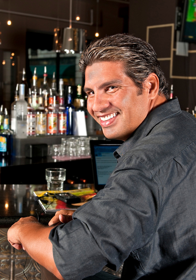 Young man relaxes and working in a bar.