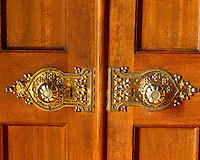 A pair of ornate door knobs decorate a double door