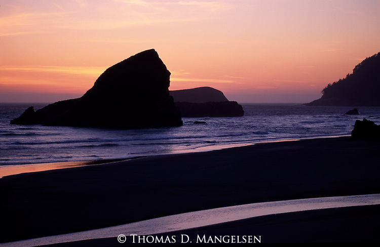 The sun sets behind sea stacks on the Oregon coast in Pistol River State Park.